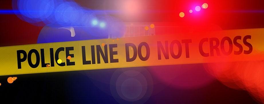 police lights behind crime scene tape