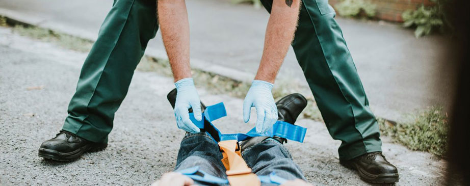 paramedic administering aid to patient on ground